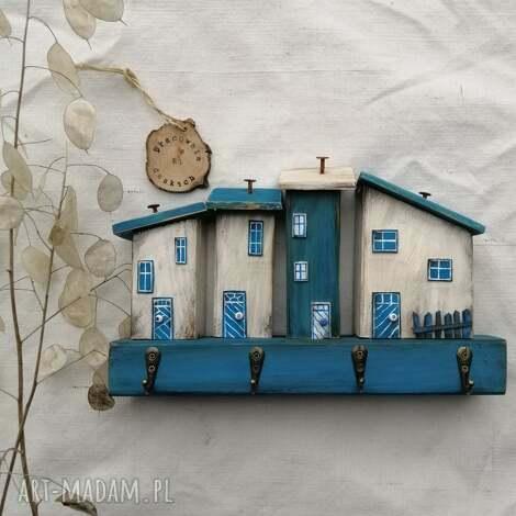 rustykalny wieszak z domkami w odcieniach niebieskobiałym, dom domek