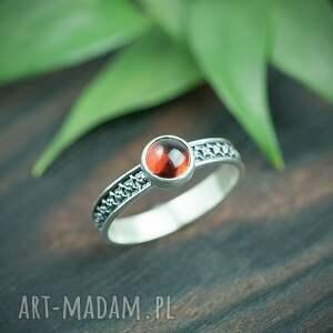 srebrny pierścionek z granatem i zdobioną obrączką, czerwonym