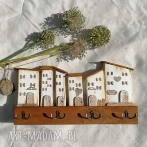 pracownia na deskach wieszak z białymi domkami, dom domek, drewniany