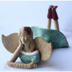 anioł leżący rozmarzony z kwiatkiem we włosach, ceramika, anioł