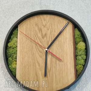 duży zegar w stalowej obręczy z dębową tarczą i chrobotkiem reniferowym