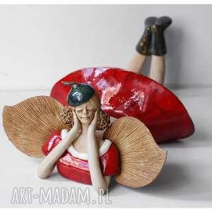 anioł leżący w czerwonej sukni i beretce, ceramika, anioł