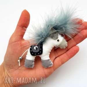 Białty konik z siodłem broszka filcu i piór, koń, filc, broszka, siodło, pióra,
