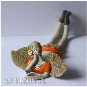 anioł leżący z książeczką i kwitkiem we włosach, ceramika, anioł, książka